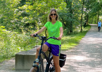Young lady riding electric bike on a bike trail
